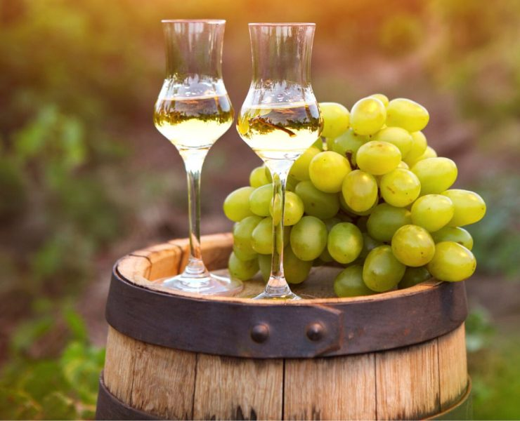 wine barrel with italian grappa wine and green grapes
