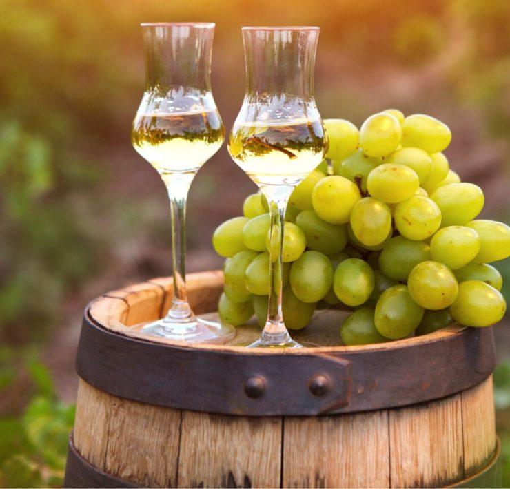 wine barrel with italian grappa wine and green grapes
