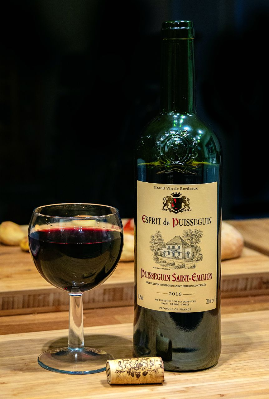 glass of red wine from Bordeaux with saint emilion bottle next to it