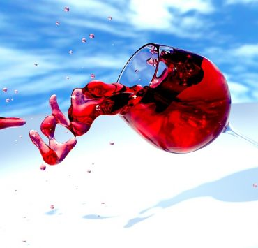red wine spilling out of a glass conceptual note