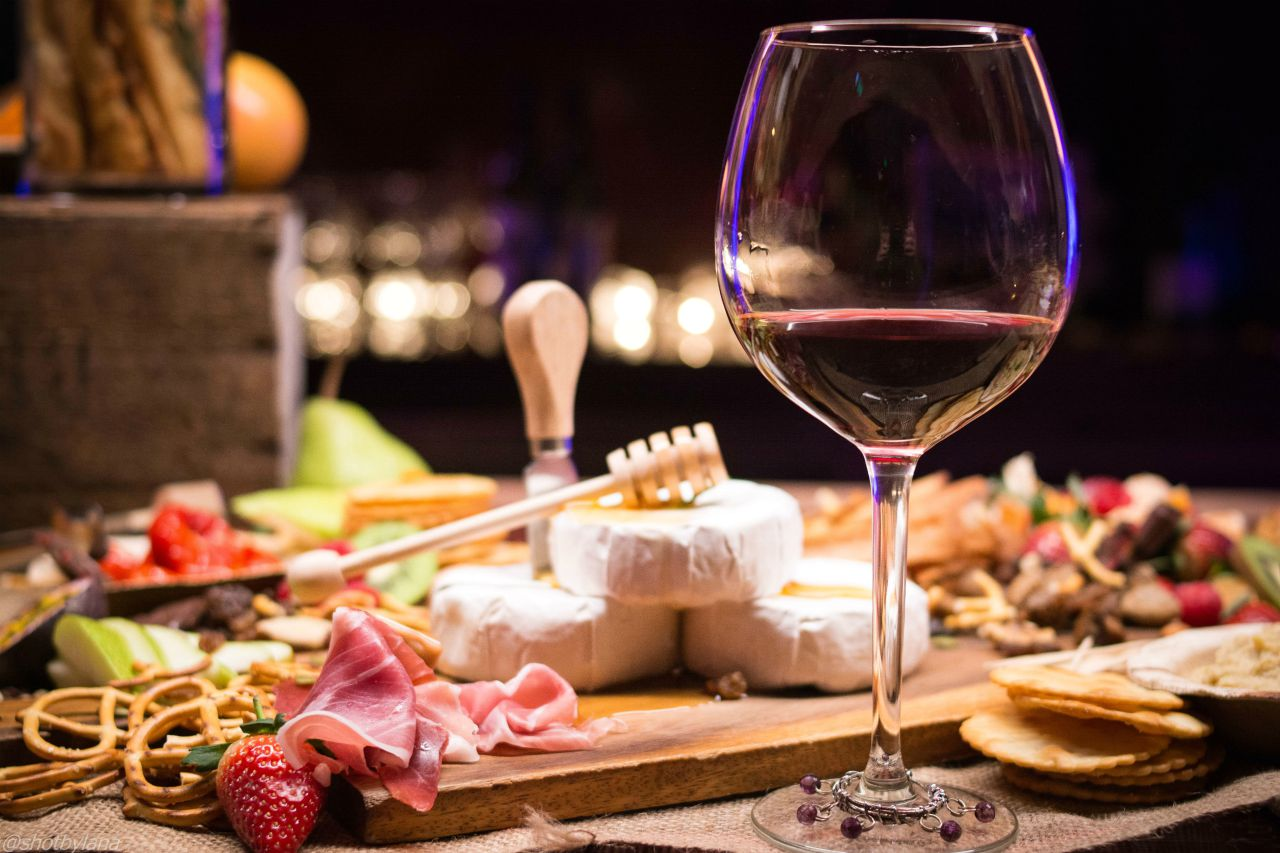cheese board with bacon and glass of white wine