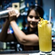 female bartender shaking cocktail in the background with a yellow cocktail in front