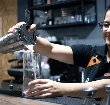 female bartender behind the bar pouring drinks